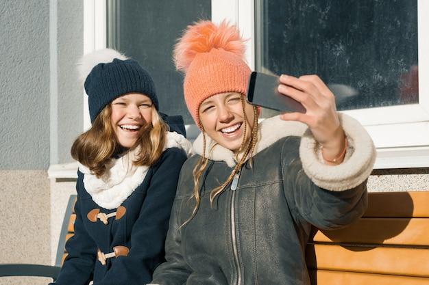 Две молодые девочки-подростки веселятся на свежем воздухе