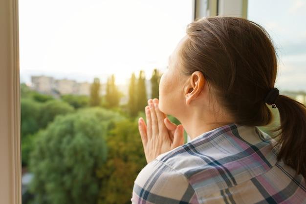 窓の外を見て成熟した女性