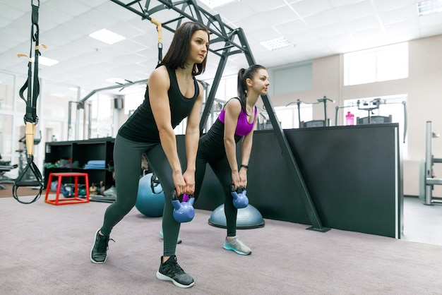 Две молодые здоровые женщины делают упражнения с весом