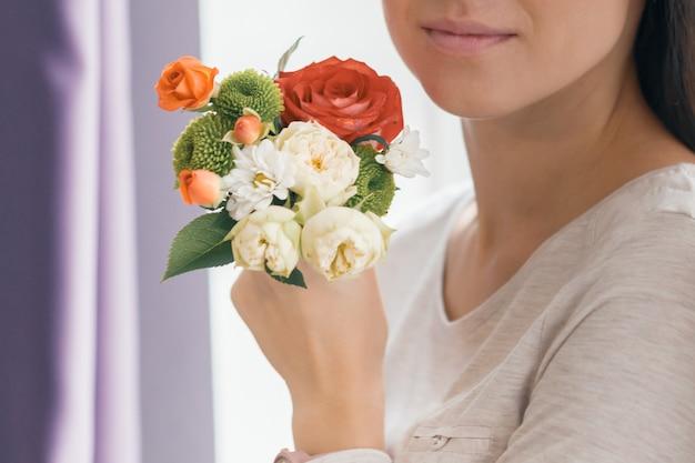 手に若い笑顔の女性の花束の花のクローズアップ