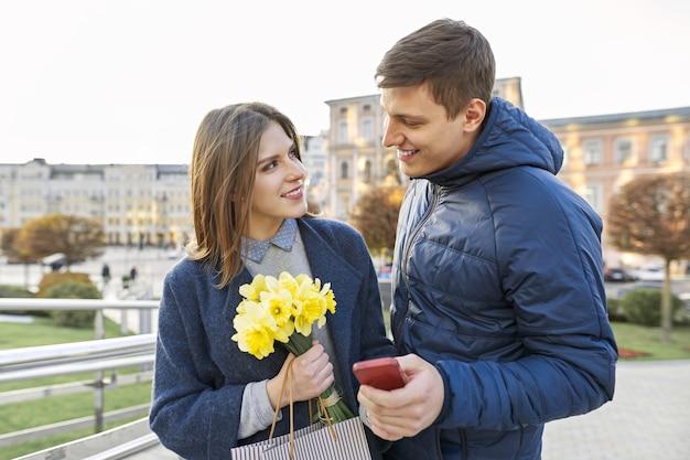 若い男と黄色の花の花束を持つ女性