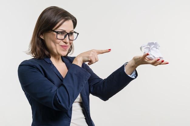 しわくちゃの紙のボールを手に持った女性