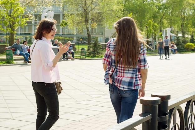 女友達が通りを歩いて話す