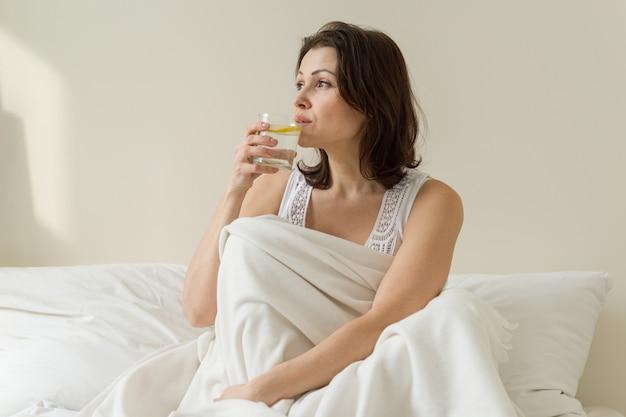 女性はベッドの上のレモンと水を飲む