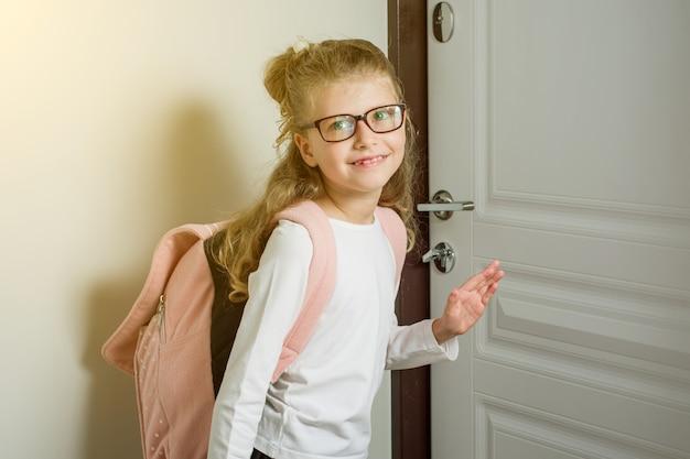 Симпатичная младшая школьница со светлыми волосами идет в школу
