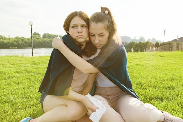 Девочка-подросток успокаивает свою плачущую и расстроенную подругу
