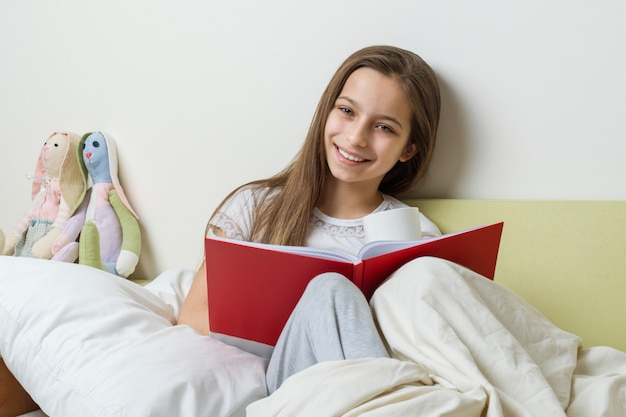 自宅で学校のノートとベッドに座っている女の子