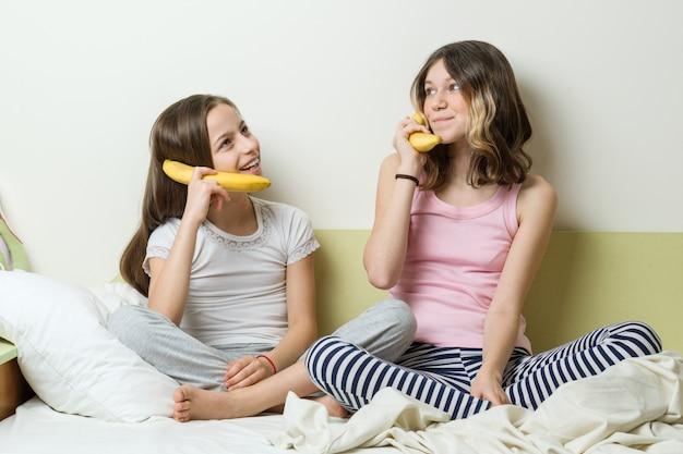 女の子は電話をし、バナナパイプを通して互いに話します