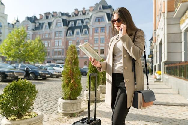 Молодая красивая деловая женщина с чемоданом путешествия