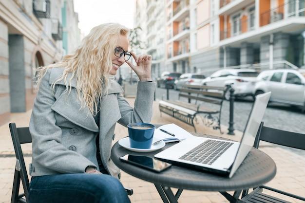 ラップトップコンピューターで屋外カフェに座っている暖かい服装で金髪の女性