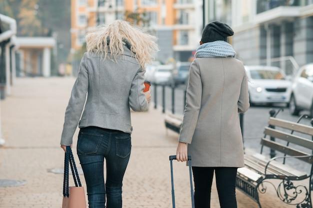 Две молодые женщины в теплой одежде гуляют с чемоданом