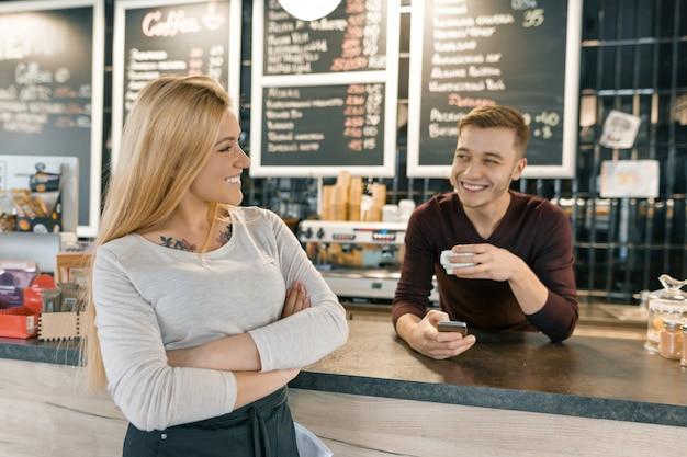 コーヒーショップの労働者の若い笑顔カップル