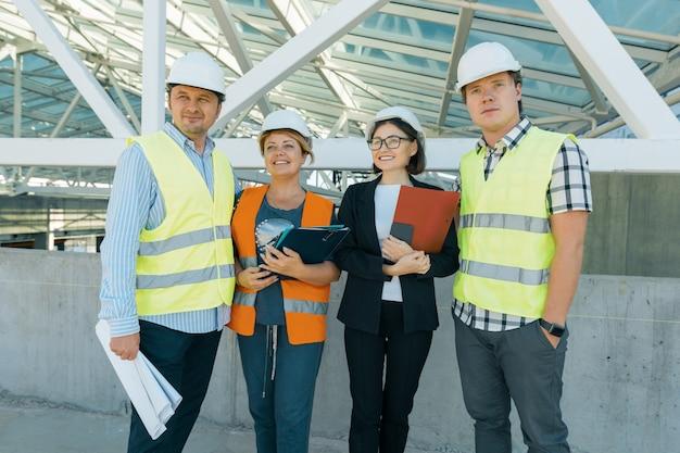 Группа инженеров, строителей, архитекторов на строительной площадке.