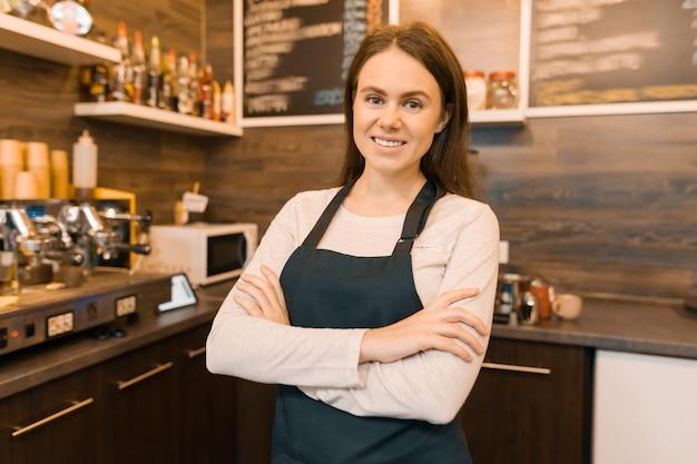 笑顔の若い女性のコーヒーショップの所有者の肖像画