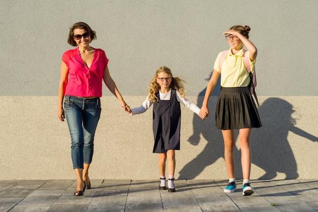 Счастливая семья, мама и дочери идут в школу, начинают учиться