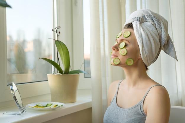 顔にキュウリの自然な自家製マスクを持つ女性