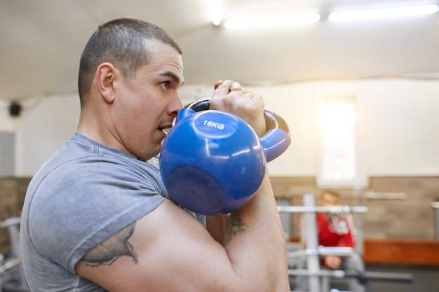 若い強い筋肉アスリートボディービルダーは重量を持ち上げる