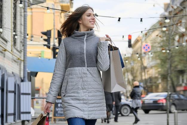 ショッピングバッグと街を歩いている美しい少女