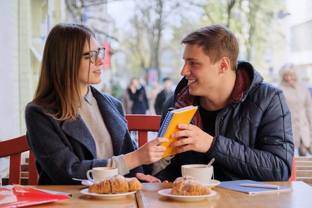 学生の若いカップルが屋外カフェで勉強します