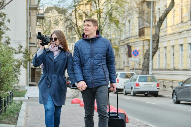 カメラが付いている都市の若い男性と女性のブロガーのカップル