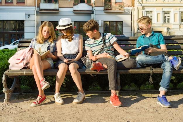 Счастливые друзья-подростки или школьники читают книги