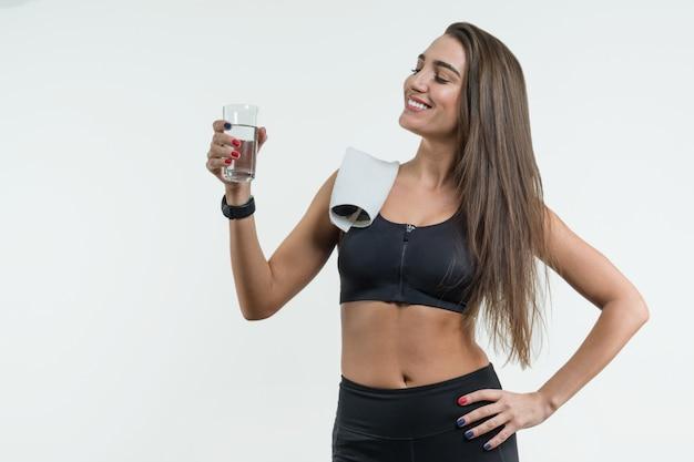 肯定的な笑顔のフィットネス女性飲料水