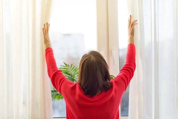 女性は窓の外を見て、カーテンを開きます
