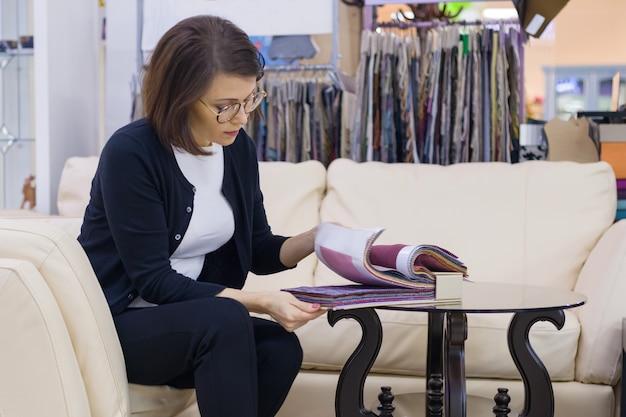 家具店の女性は、ソファ、アームチェアの室内装飾用のファブリックを選択します。