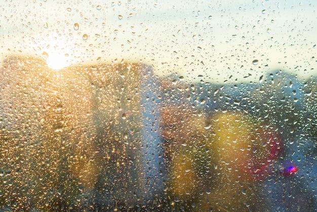 光沢のある雨の滴で背景の日当たりの良い窓