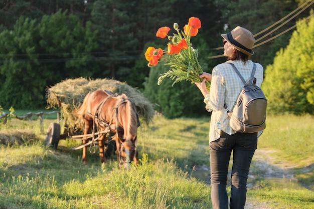 赤いケシの花の花束と帽子の女