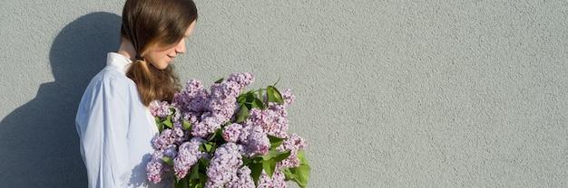 ライラックの花束を持つ若い十代の少女