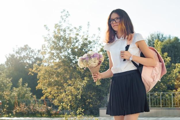 バックパックと花の花束とメガネの女子生徒