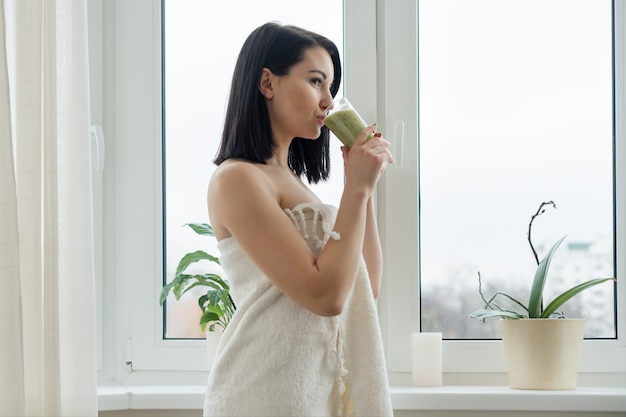 新鮮なブレンドグリーンキウイフルーツのスムージーを飲む女性