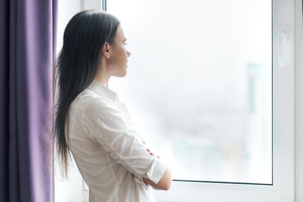 窓の外見て自信を持って若い実業家の肖像画