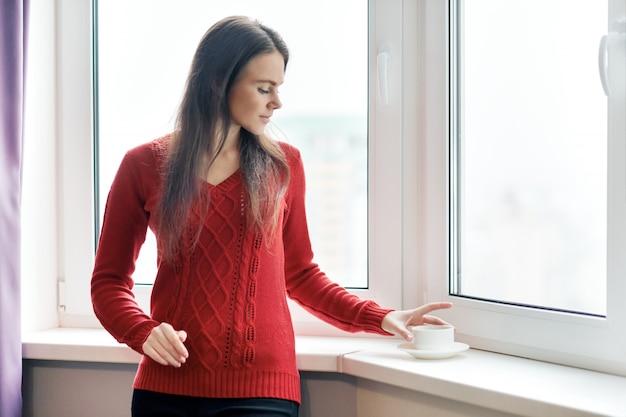 Портрет молодой красивой женщины в кофе красного свитера выпивая