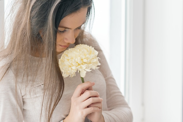 大きな淡黄色の花を持つ少女のクローズアップの肖像画