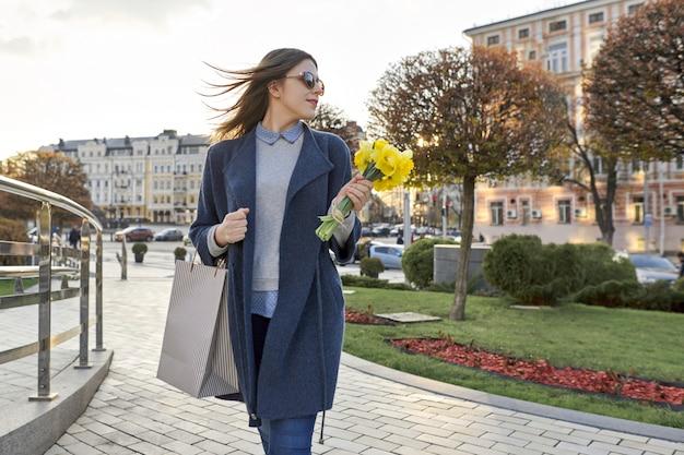 街、花と買い物袋の花束を持つ若い女性を歩く少女