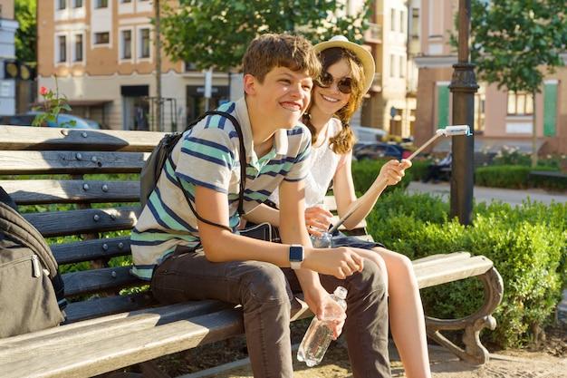 Подростковые друзья девочка и мальчик сидят на скамейке в городе, улыбаясь, разговаривая