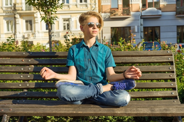 Подросток сидит в позе лотоса на скамейке в городском парке. расслабься, отдохни, медитация.