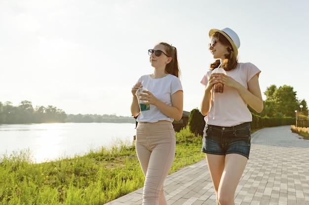 ガールフレンドは、自然の中で公園を歩いています。