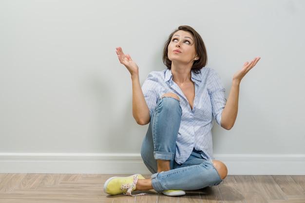 空白の上に座って質問について考える大人の女性のクローズアップ