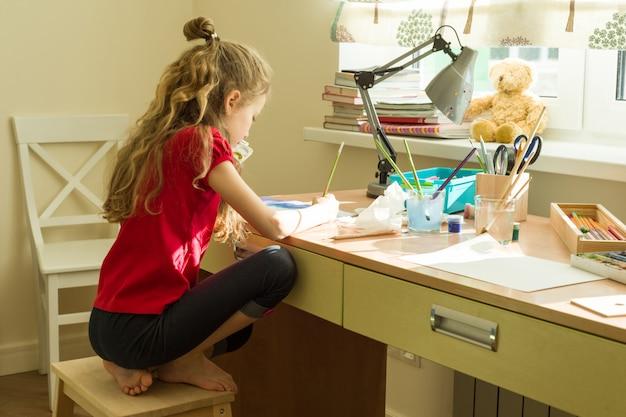 女児は自宅のテーブルで水彩を描画します