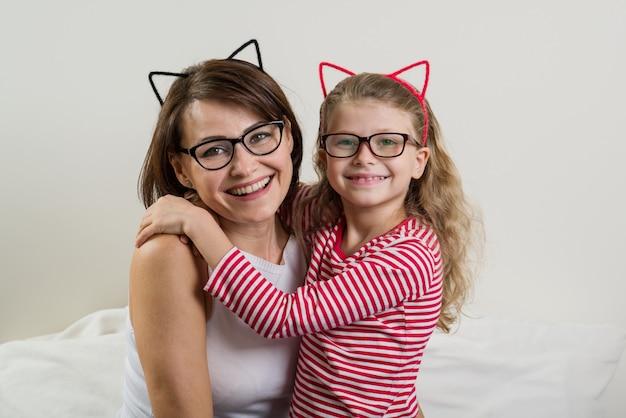 娘は愛情を込めて母親を抱きしめます。メガネの親子。
