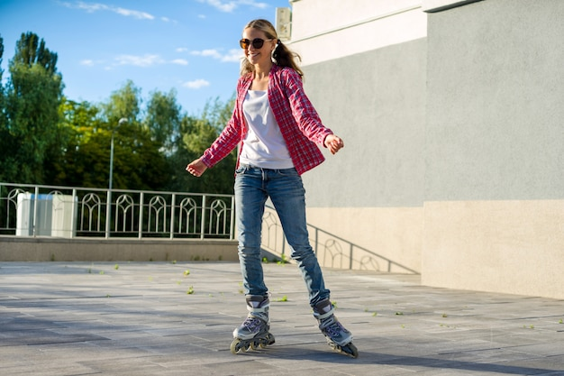 クワッドローラースケートでアクティブなスポーツ十代の少女