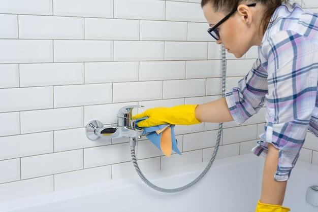 Женщина убирает в ванной комнате дома
