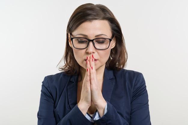 メガネの女性実業家は目を閉じて、祈り、瞑想します。