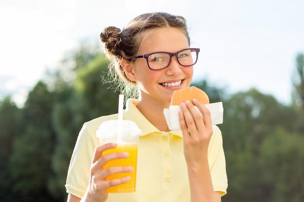 Милая улыбающаяся девочка-подросток держит гамбургер и апельсиновый сок