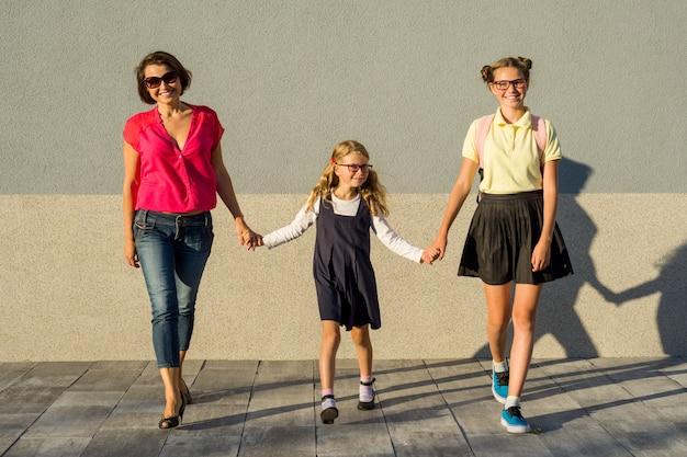 Мать и дочь школьницы, держась за руки