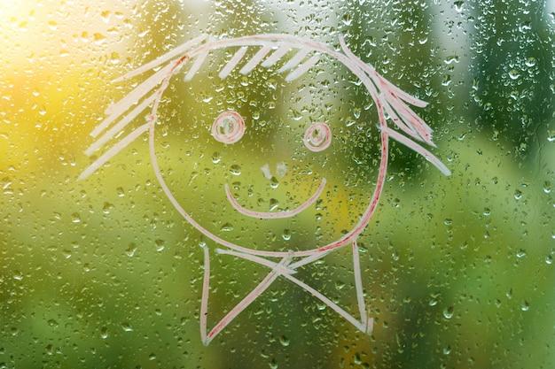 雨の秋の窓にポジティブスマイリー