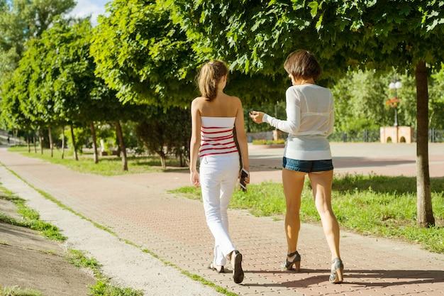 母と娘のティーンエイジャーが歩く